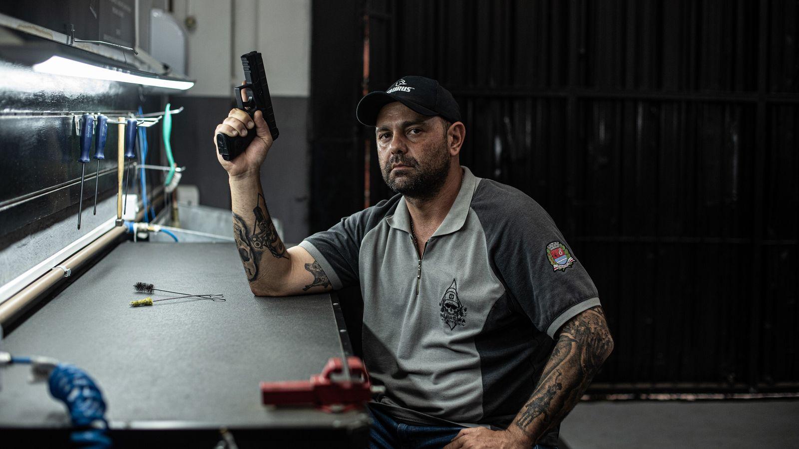 O CAC Danilo Caruso, 40, empunha uma pistola na mesa que utiliza para a manutenção de ...