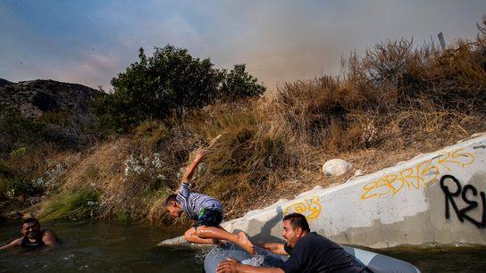 Eddie Lopez e seu filho, Eddie Jr., brincam próximo a um tubo de drenagem no rio ...