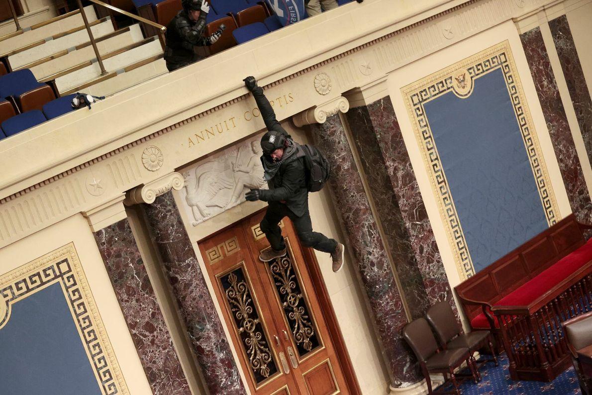 Apoiador de Trump é visto pendurado em um dos balcões da câmara dos senadores.