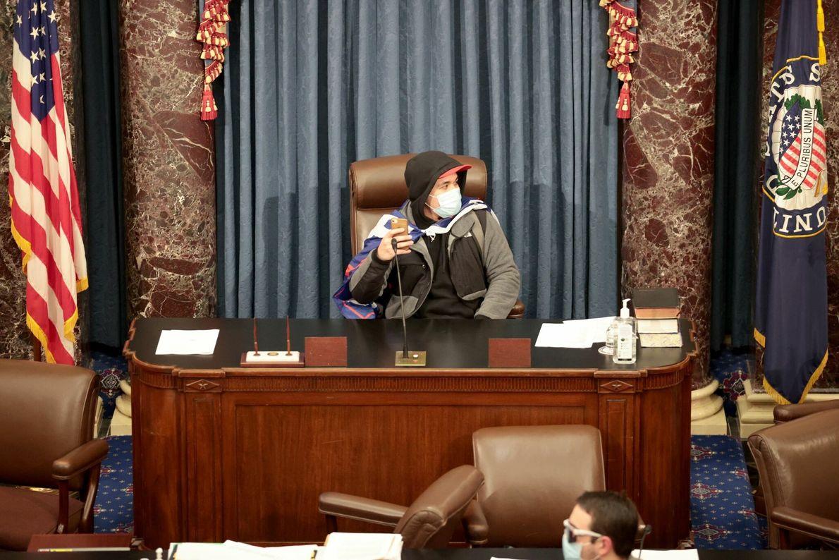 Um manifestante sentou na mesa do presidente do senado depois que parlamentares interromperam a certificação da ...