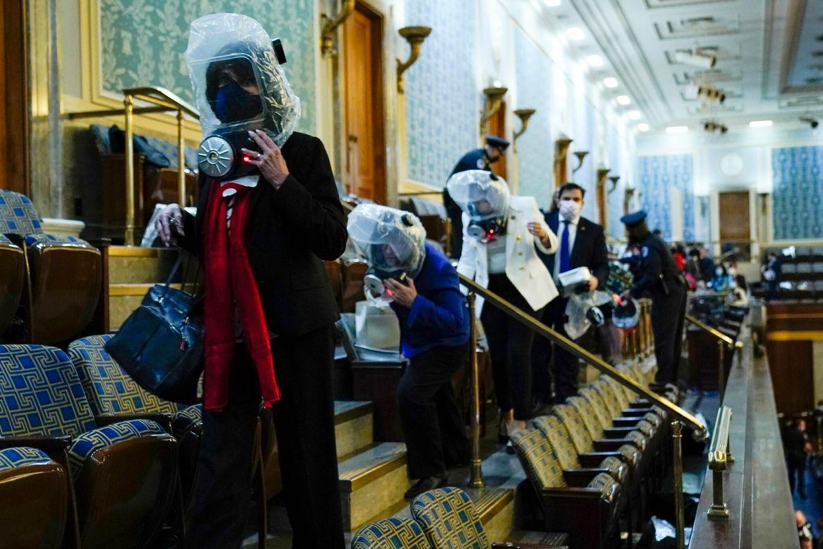 Enquanto apoiadores do presidente Trump invadiram o capitólio, congressistas e funcionários na plateia da câmara dos ...