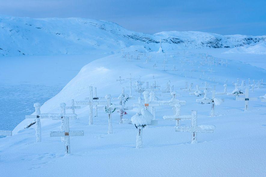 Cruzes do cemitério estão cobertas de neve em Upernavik, na Groenlândia.