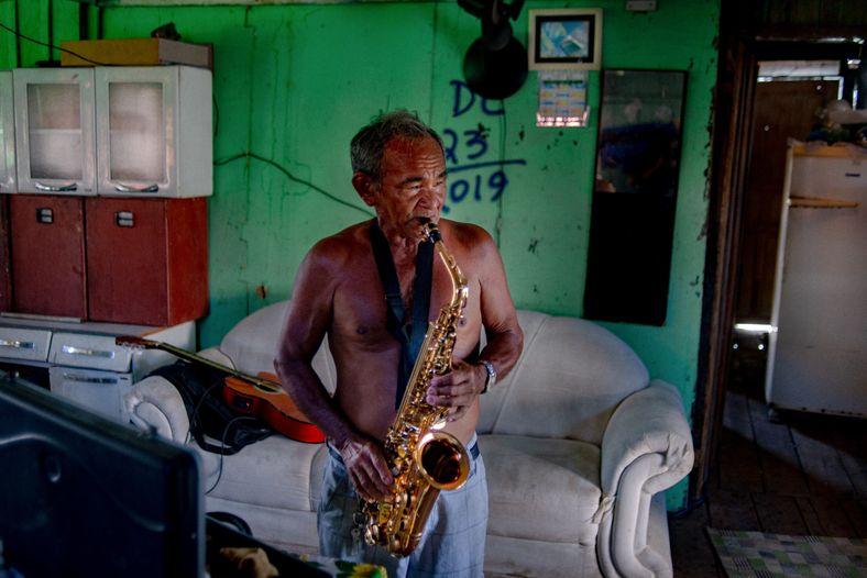 foto de homem sem camisa tocando saxofone dentro de casa