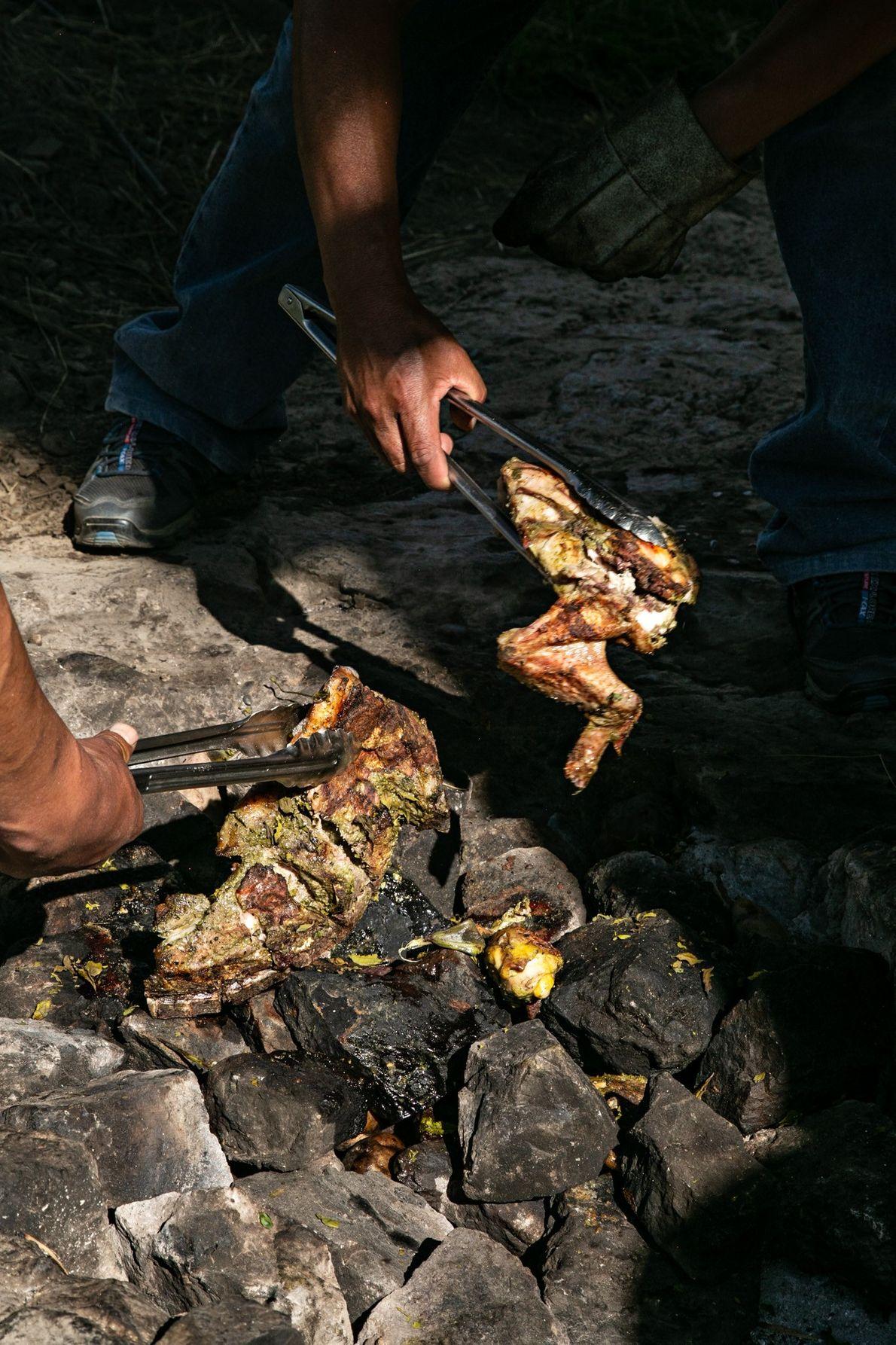 Porco, frango e cordeiro são retirados do fogo pachamanca, no jardim orgânico de El Albergue em ...