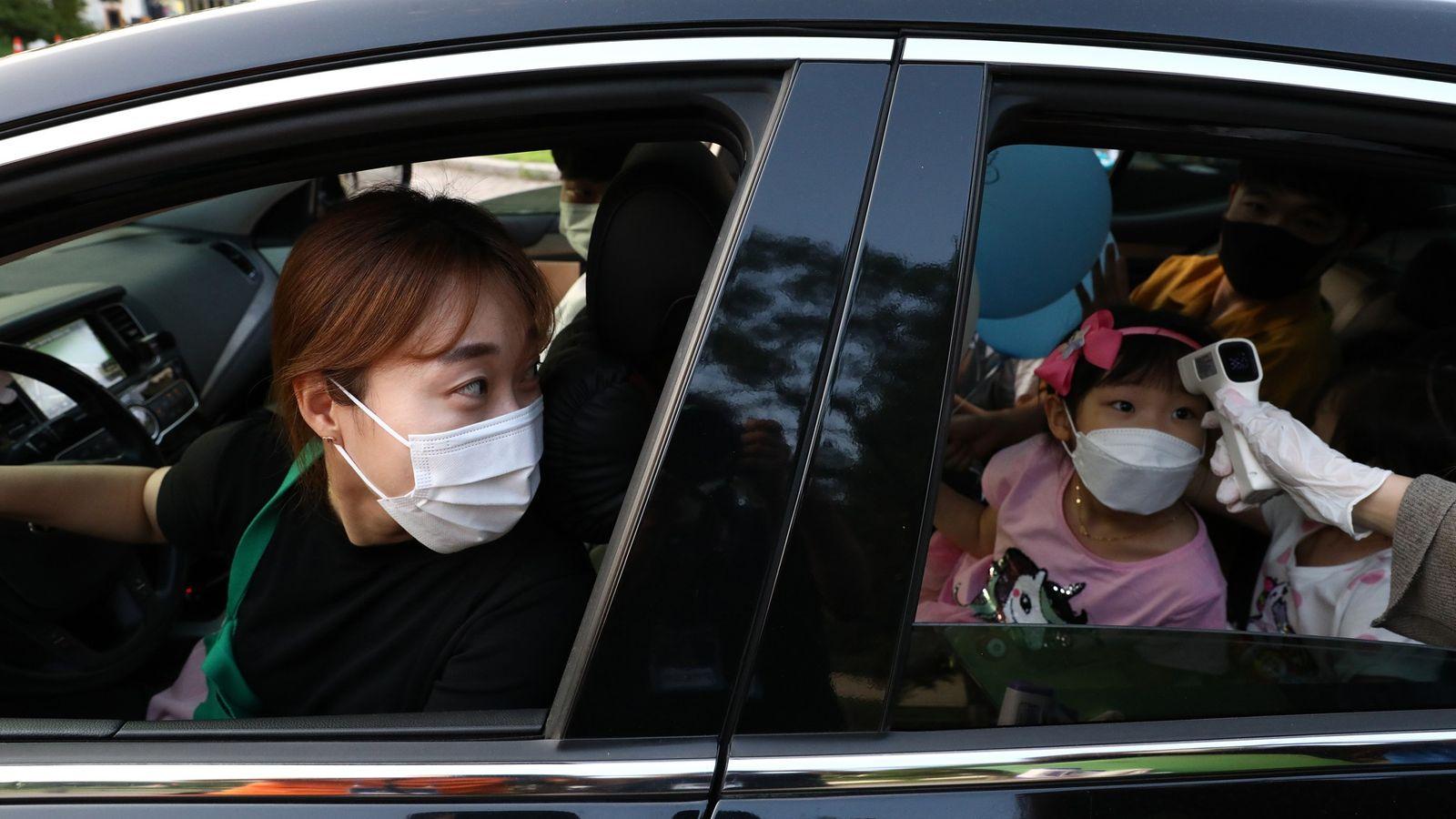 Uma mãe observa a temperatura de sua filha sendo aferida no carro, na Coreia do Sul. ...