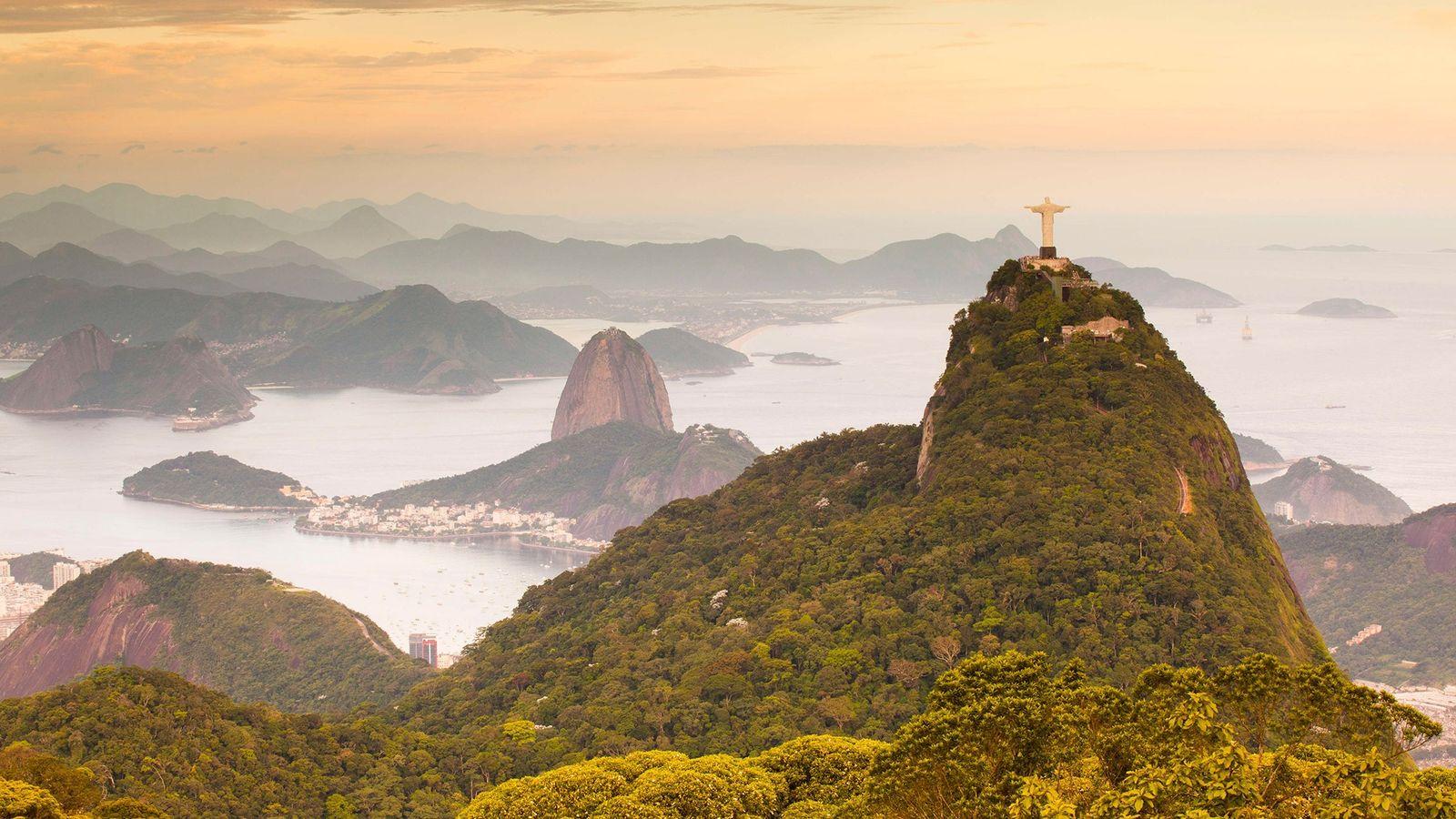 A famosa estátua do Cristo Redentor, cercada pela Floresta da Tijuca, contempla o Rio de Janeiro ...