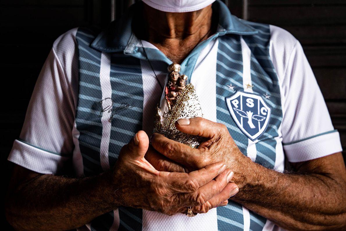 foto de homem com uniforme do time de futebol Paysandu segurando imagem de uma santa