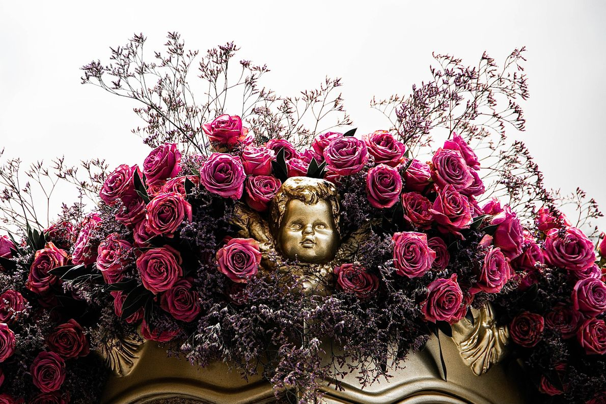 Foto de estátua de anjo em meio aa flores na berlinda de vidro que protege a ...