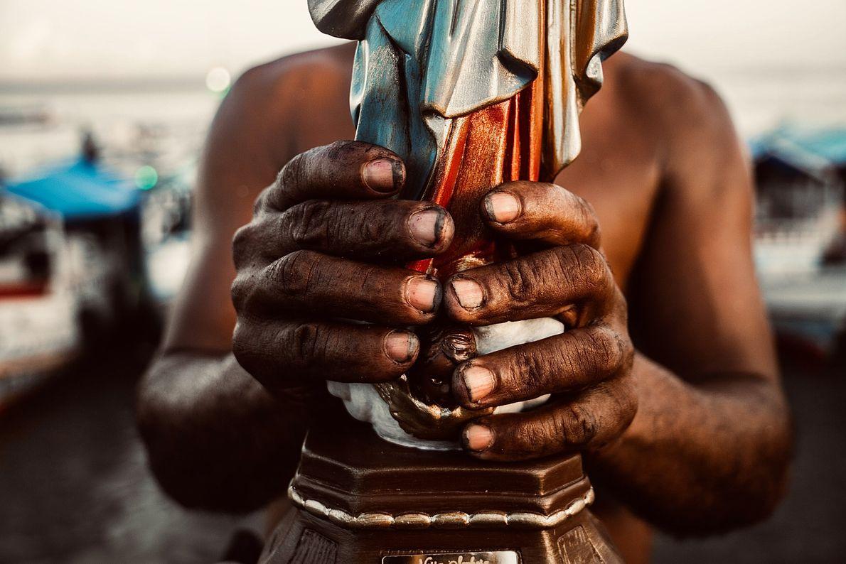 Foto das mãos de um homem segurando imagem de uma santa
