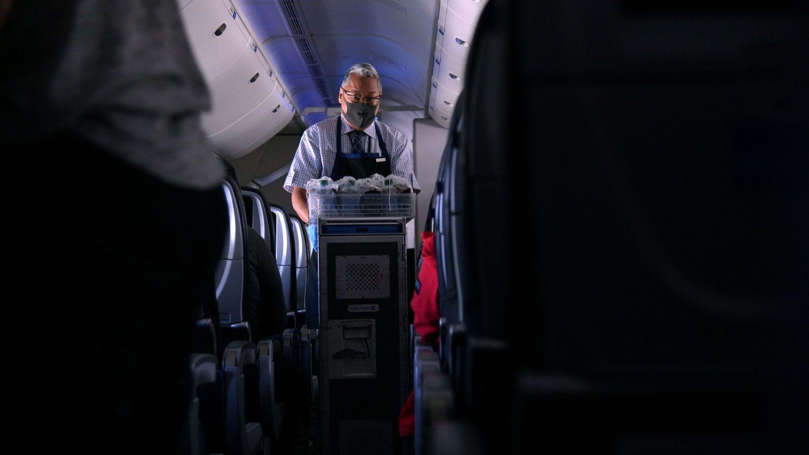 Um comissário de bordo utilizando máscara entrega comidas e bebidas em um voo de São Francisco, ...