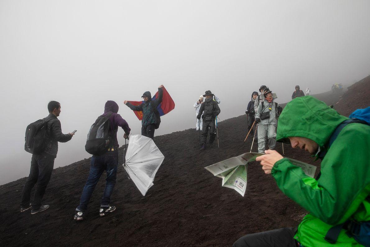 Um grupo de alpinistas percorre a trilha Monte Fuji-Yoshida no Japão.