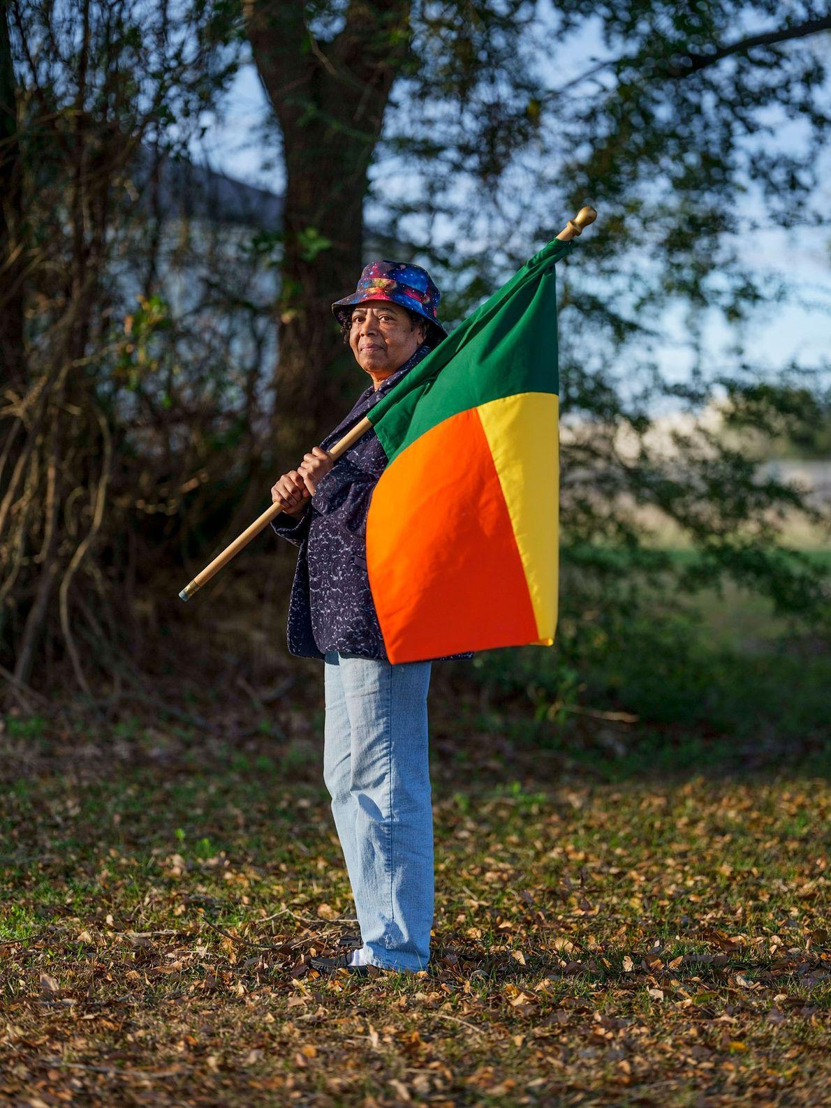 Patricia Frazier segura a bandeira do Benin, a nação moderna que já foi governada pelo rei ...
