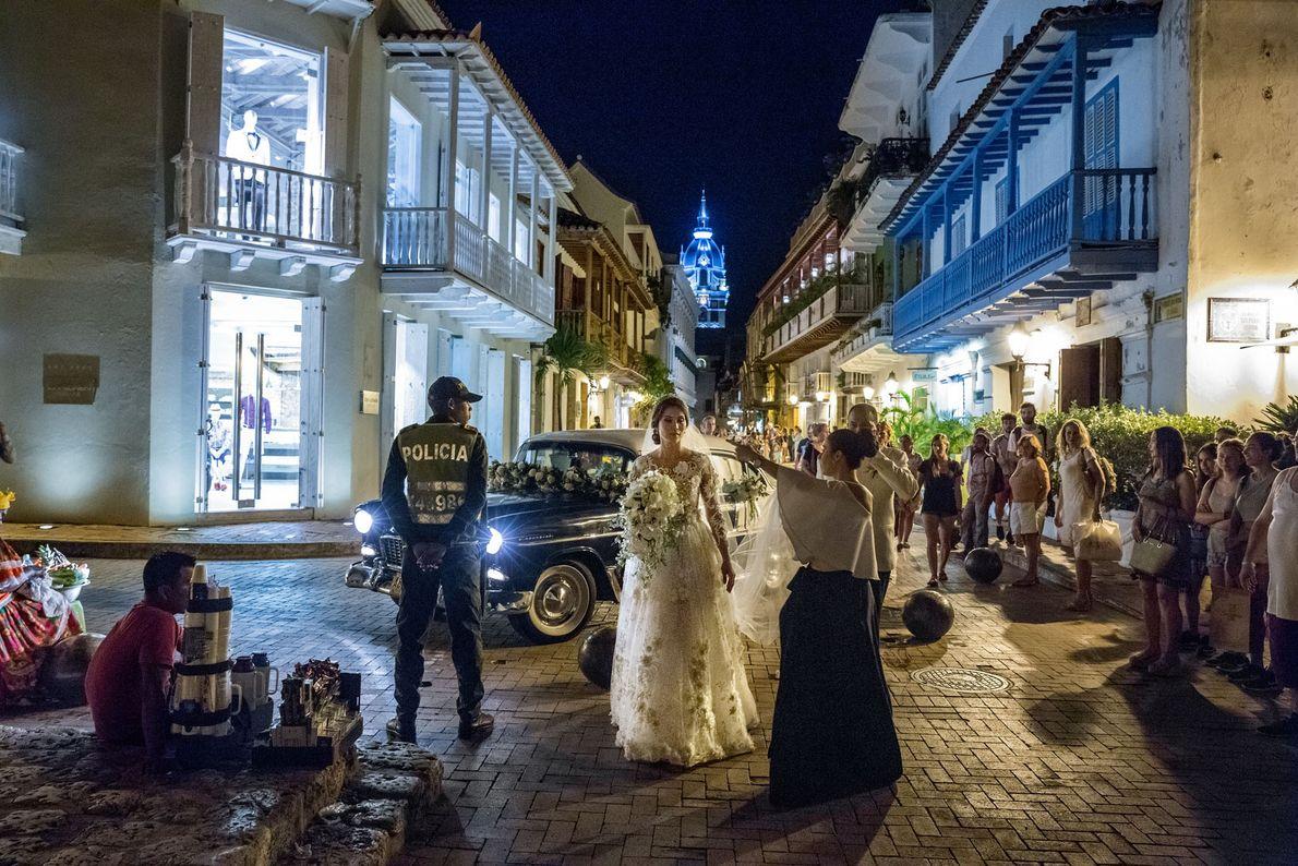 Pedestres assistem à chegada dos convidados de um casamento na Igreja de San Pedro Claver, no ...