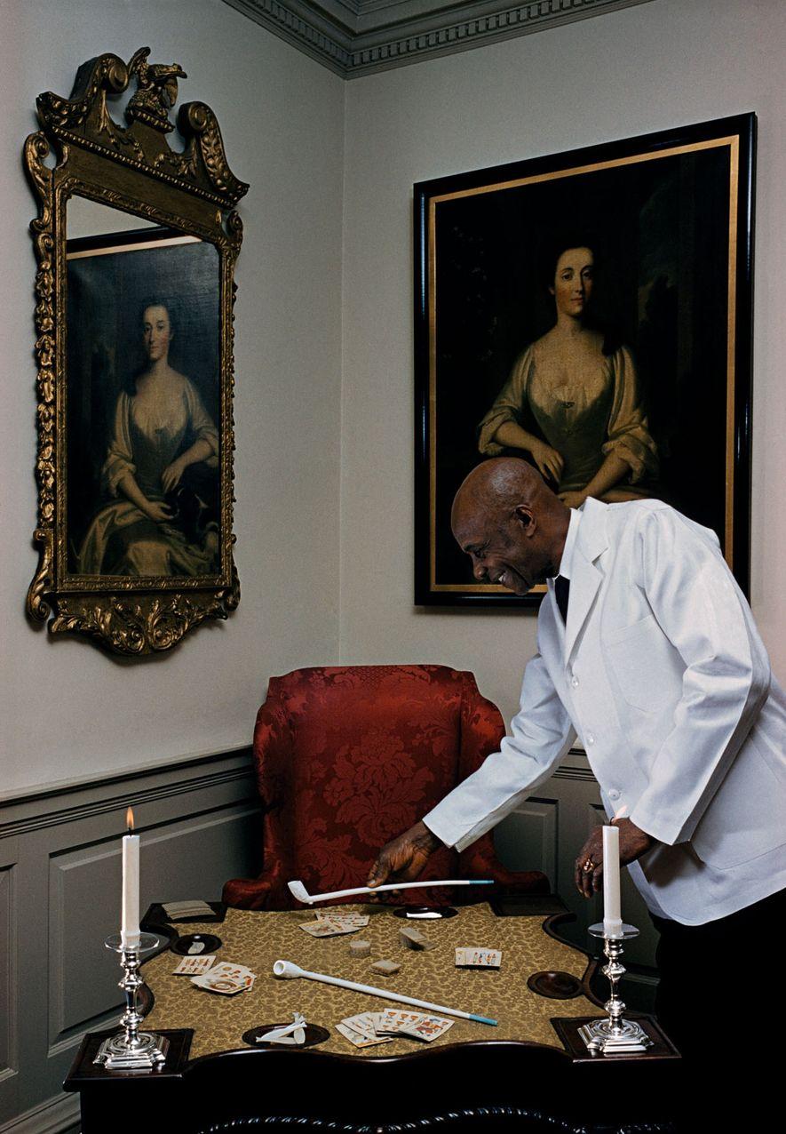 """""""Baralho e cachimbos entretêm os convidados no salão da Fairfax House, do século 18"""", diz a legenda em um artigo de 1956 sobre o estado da Virgínia. Embora as mansões mencionadas tenham sido construídas com o trabalho escravo, o redator ressaltou que elas """"constituem um capítulo da história do qual todo americano se recorda com orgulho""""."""