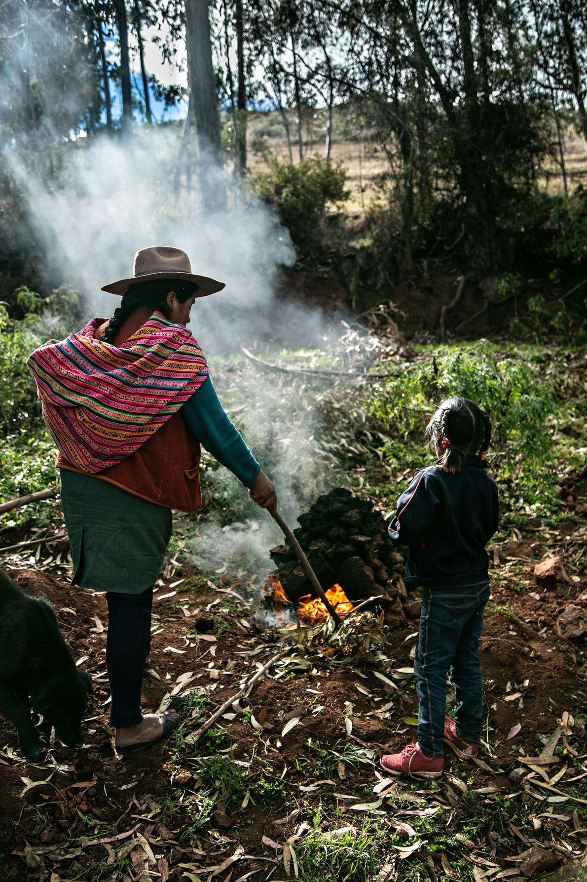 Claudia Carihuman toma conta do huatia, onde batatas e feijões-fava serão assados.