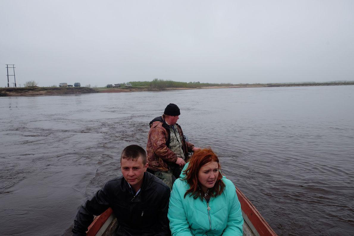 Jovem casal de Byechye cruza o Rio Mezen a bordo de um barco rocketa.