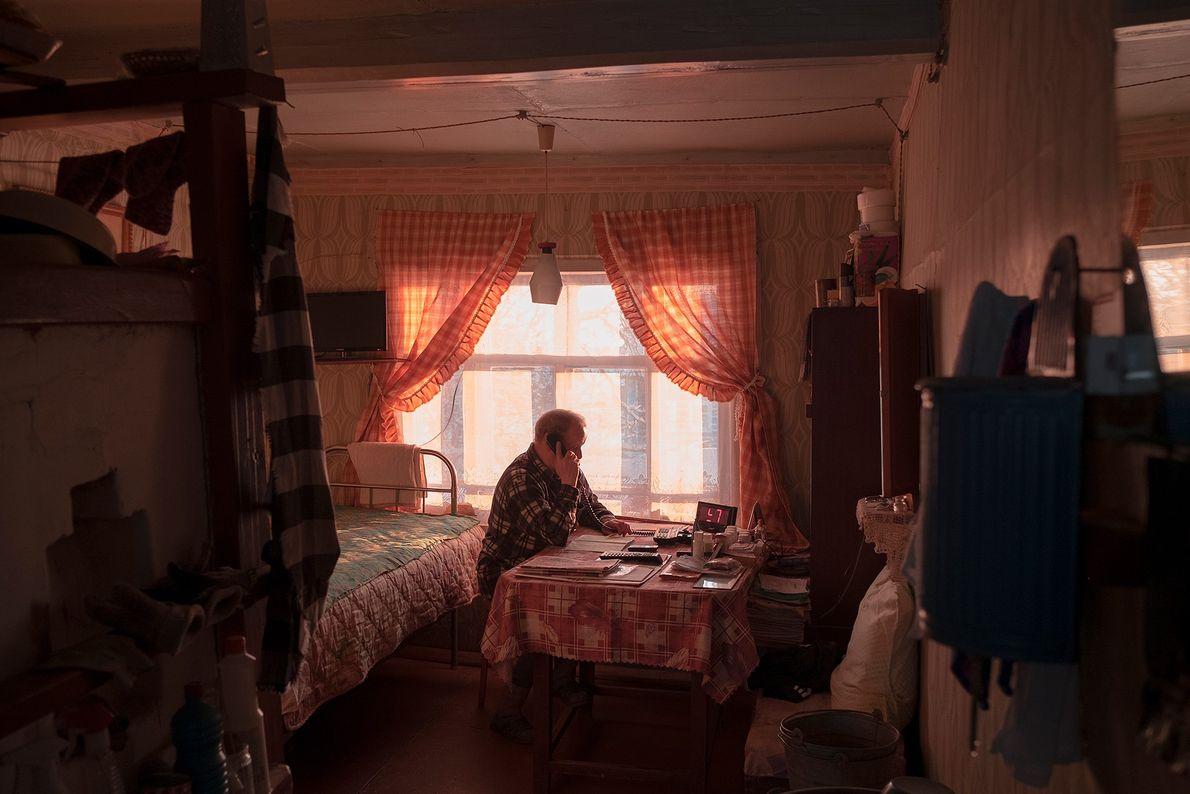 Vladimir, 76 anos, morador de Sovpolie, fala ao telefone em sua casa.