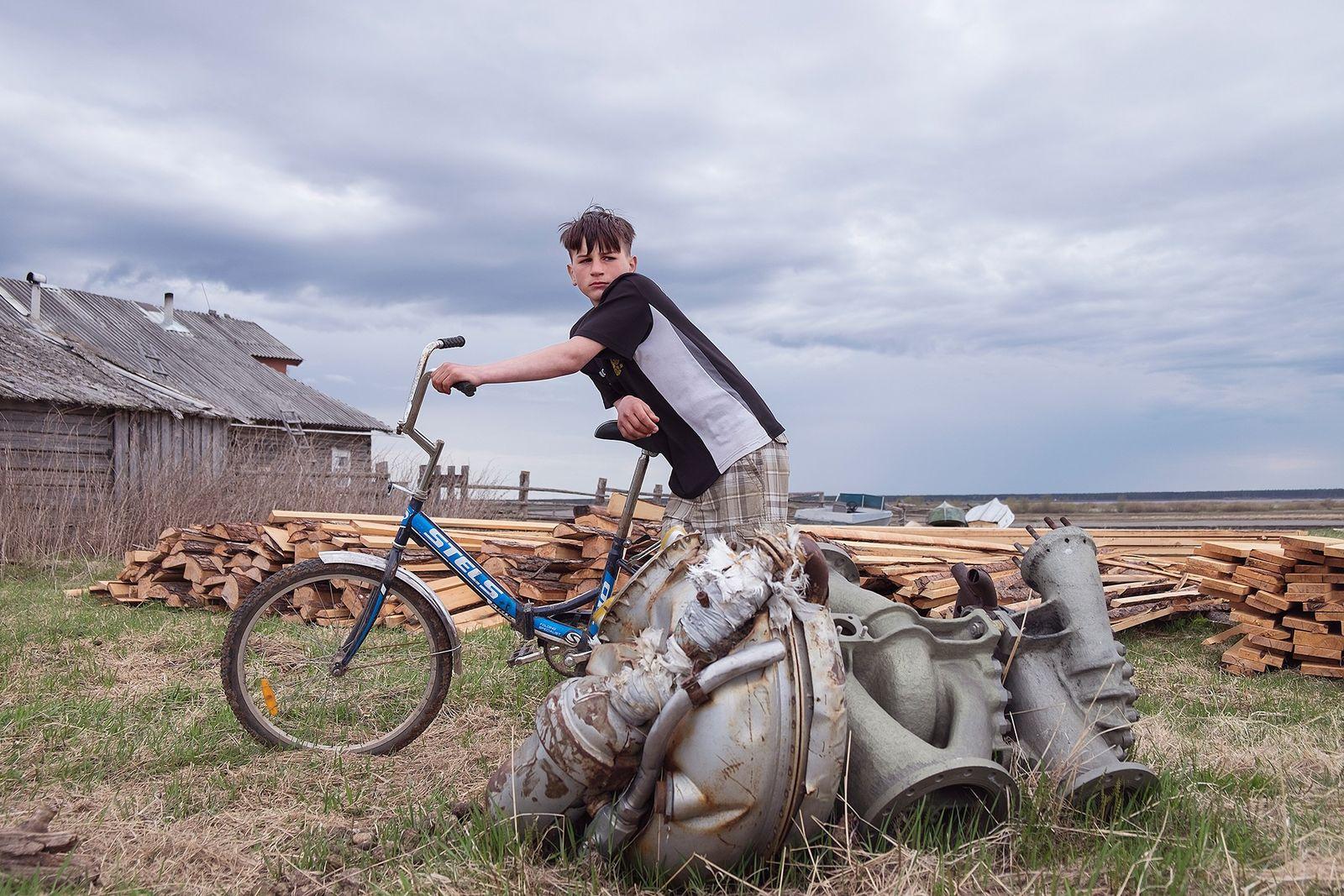 Anton, 13 anos, de pé próximo ao pedaço de um foguete no vilarejo de Dolgoshecheye, no ...