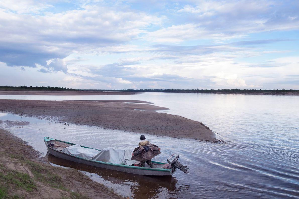 Um pescador em seu barco rocketa desembarca com sua carga. Ele mora em uma localidade com ...