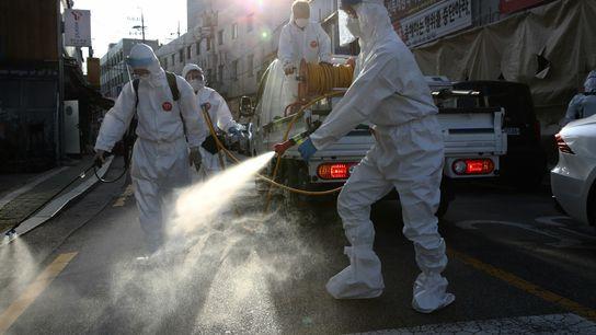 Equipe de desinfecção, usando equipamentos de proteção individual, limpa rua para evitar a propagação do coronavírus ...