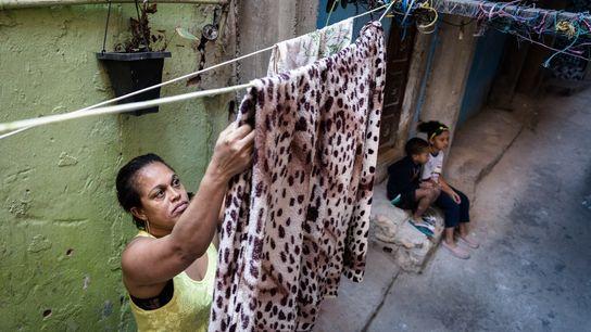 A trabalhadora doméstica desempregada Ailde de Oliveira Dourado estende as roupas de sua família no beco ...