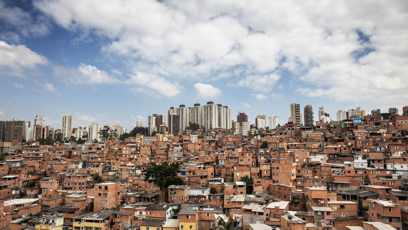 A imensa favela de Paraisópolis, lar de mais de 100 mil pessoas, é cercada por arranha-céus ...