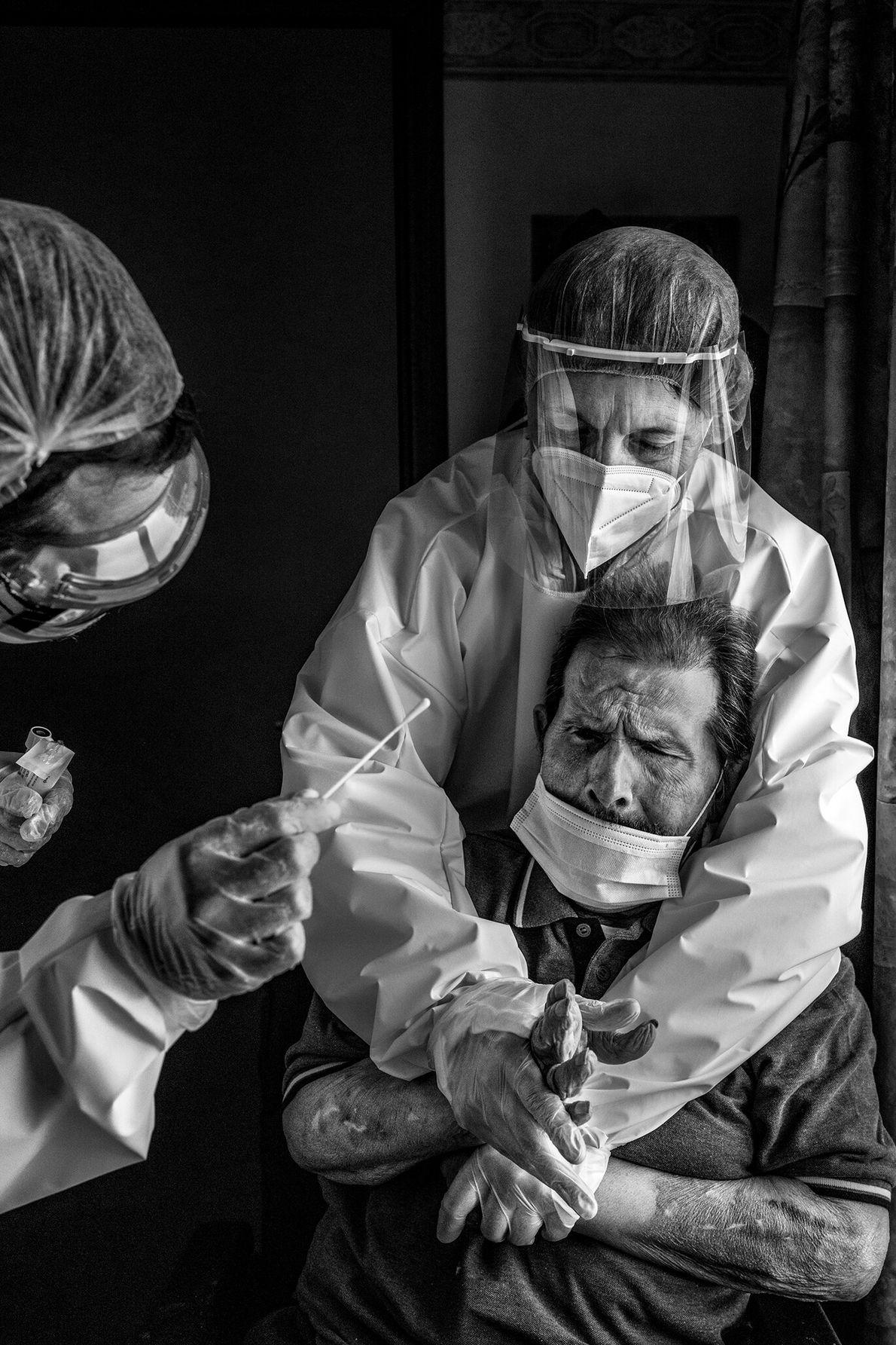 Em uma casa de repouso em La Louviere, na Bélgica, uma enfermeira segura um morador para ...