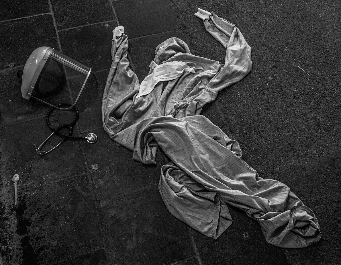 Estetoscópio, vestimenta e equipamento de proteção individual de um médico jogados ao chão na entrada de ...