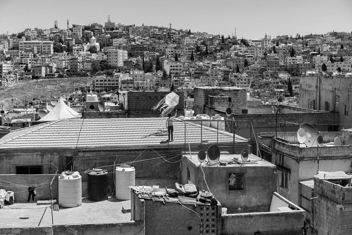 Durante o lockdown em Amã, jovem jordaniano empina pipa em um telhado. As empresas da cidade ...