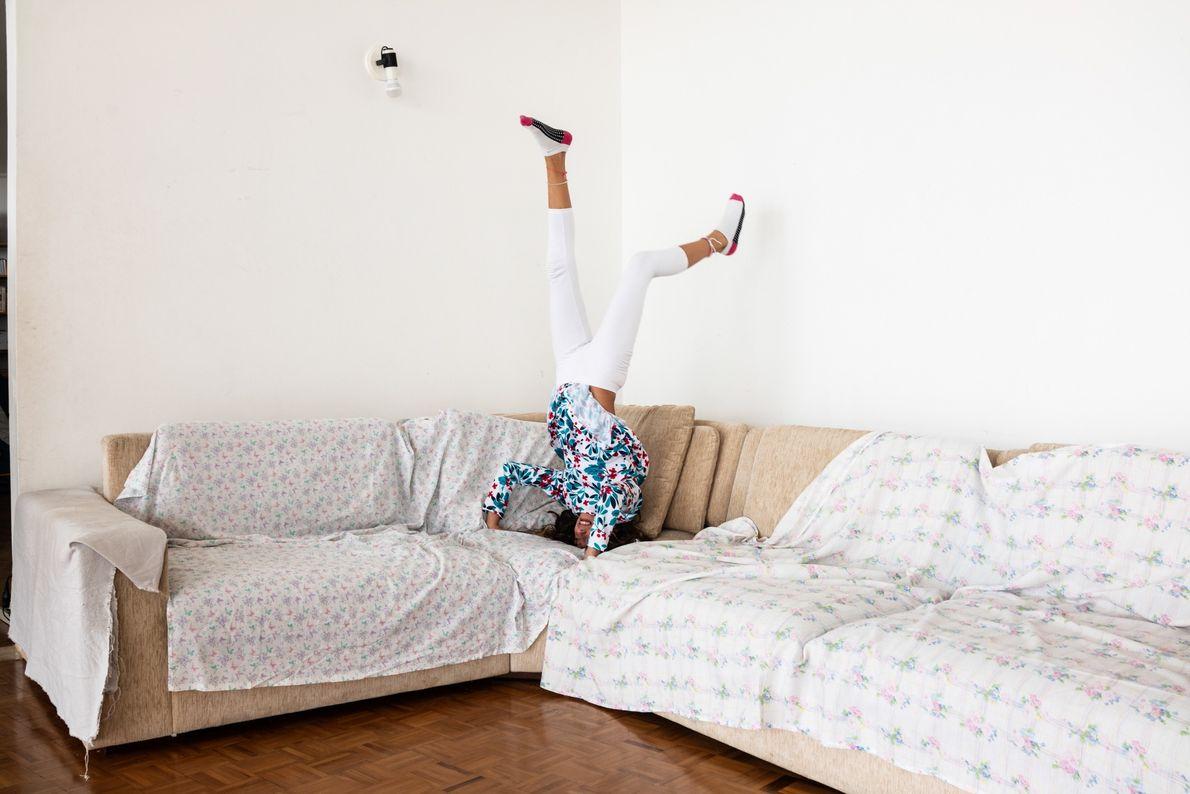 Helena Sabino, 10 anos, brinca no sofá do apartamento de sua família.