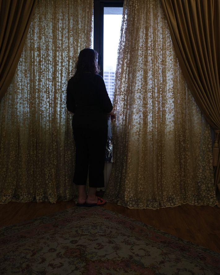 A mãe da autora, Jila, em frente à janela do quarto apreciando a árvore que floresce ...