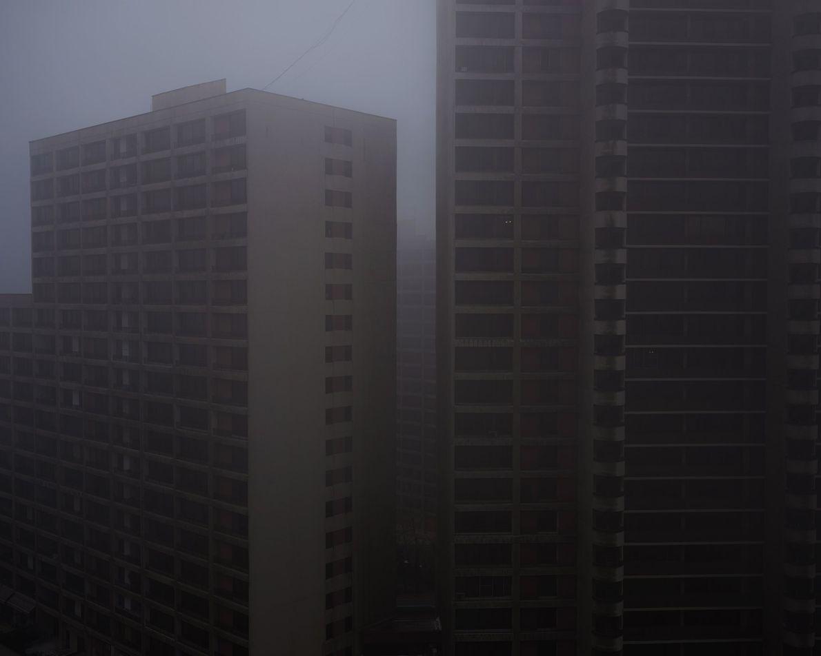 Olhando para fora da varanda, um dia nublado embaça a visão da fotógrafa.