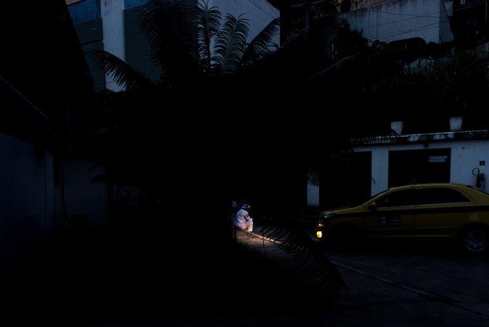 Uma profissional de saúde é iluminada, durante seu intervalo, pelos faróis de um táxi que leva ...