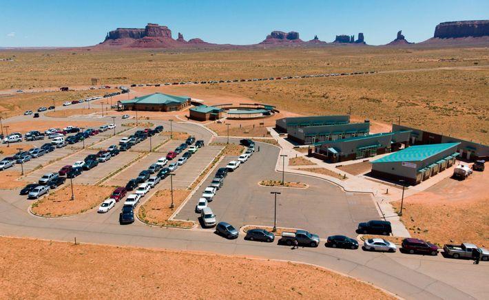 Uma fila de carros se estende ao longo da estrada em um ponto de distribuição de ...