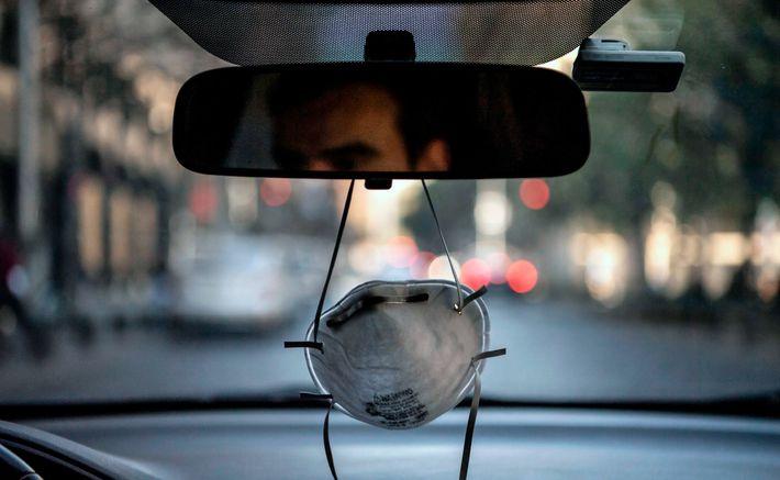 Máscara facial pendurada no espelho retrovisor de um carro em Santiago, Chile, em meio à pandemia ...