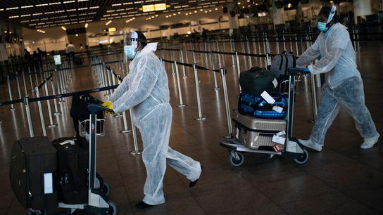 Passageiros com roupas de proteção transportam sua bagagem no Aeroporto Internacional de Zaventem em Bruxelas, na ...