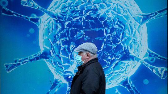 Homem usando máscara passando pela ilustração de um vírus do lado de fora do Centro Regional ...