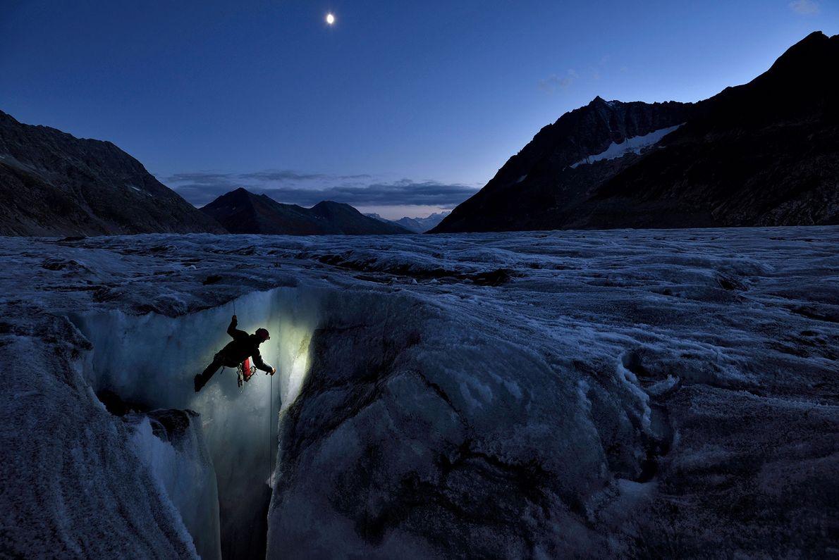 Um explorador começa uma escorregadia descida pela abertura vertical na geleira Aletsch.