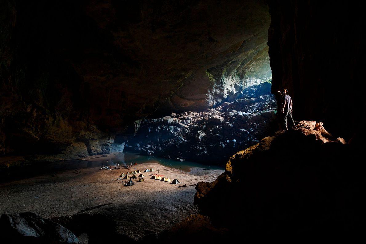 Um homem atua como vigia da noite para um acampamento dentro da caverna Hang Én, no ...