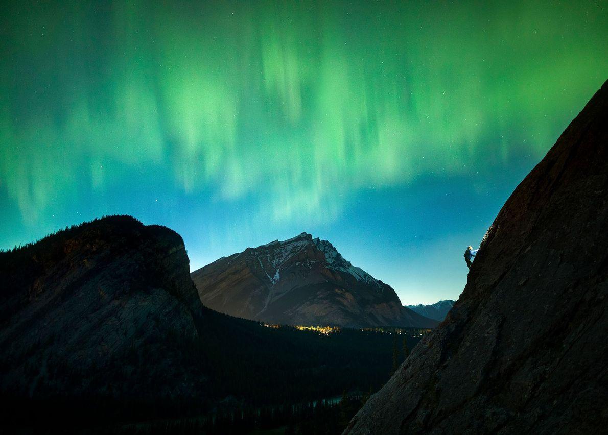 Uma aurora boreal se espalha pelo céu sobre um alpinista em Rundlehorn, no parque nacional de ...