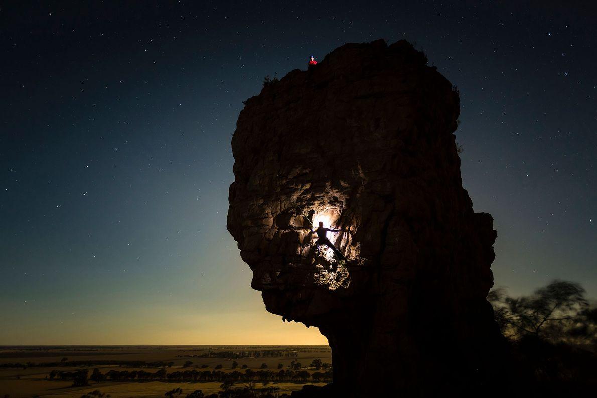 Uma alpinista ilumina o Monte Arapiles com uma lanterna enquanto ela o escala em Victoria, na ...