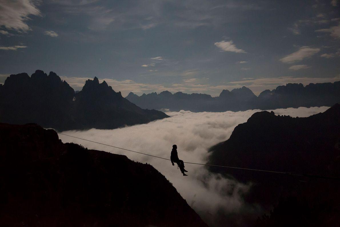Um praticante de slackline se senta sobre uma corda esticada entre picos de morros nas Dolomitas ...