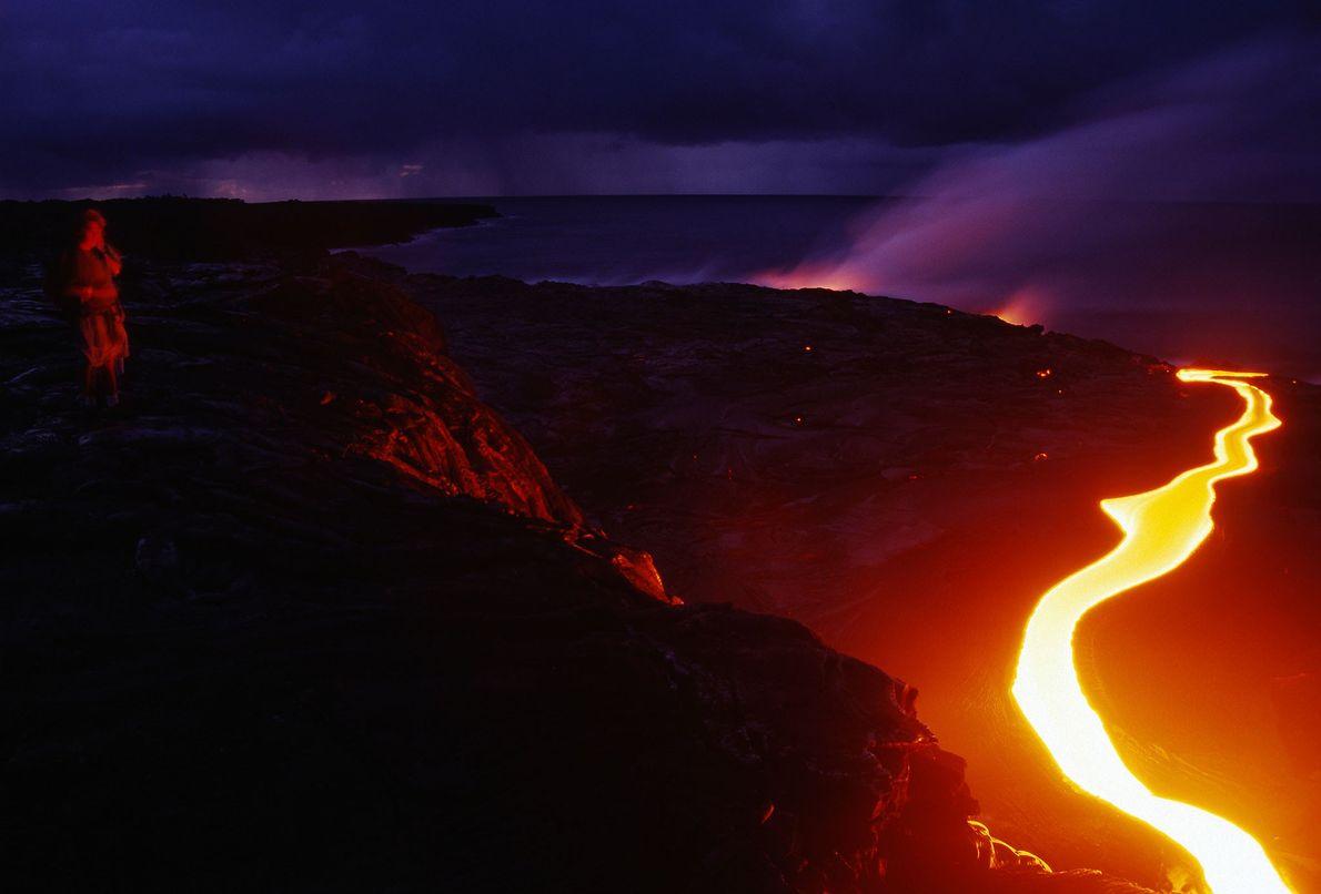 Uma mulher olha por cima de um precipício para um rio de lava perto da costa ...