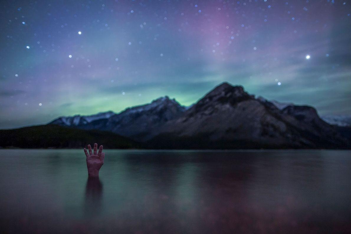Uma mão se levanta da superfície do lago Minnewanka, no parque nacional de Banff, no Canadá.