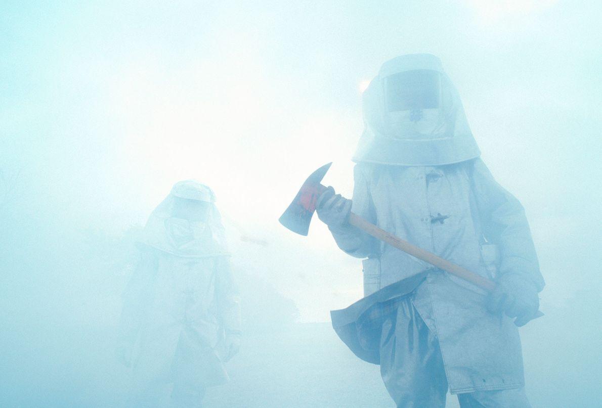 Bombeiros carregam machados por dentro de uma grossa camada de fumaça no Texas, Estados Unidos.