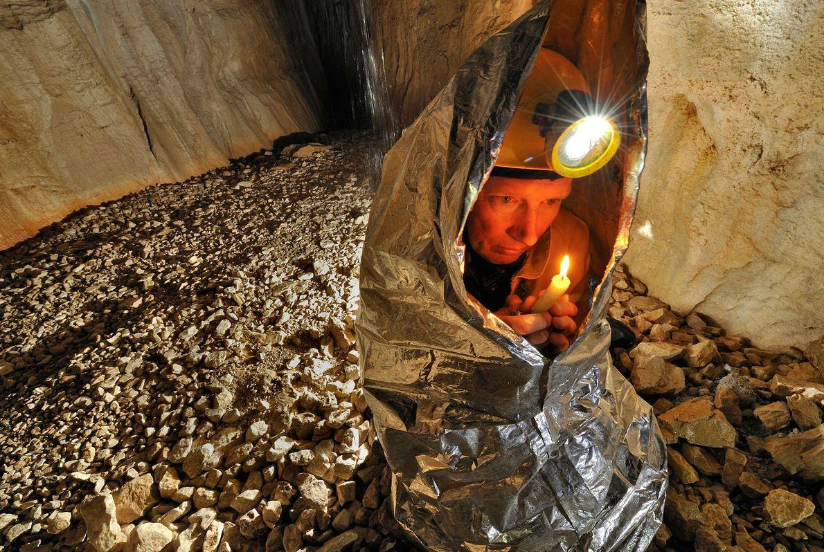 Um explorador usa uma vela e um cobertor de isolamento para tentar ficar aquecido em Gouffre ...
