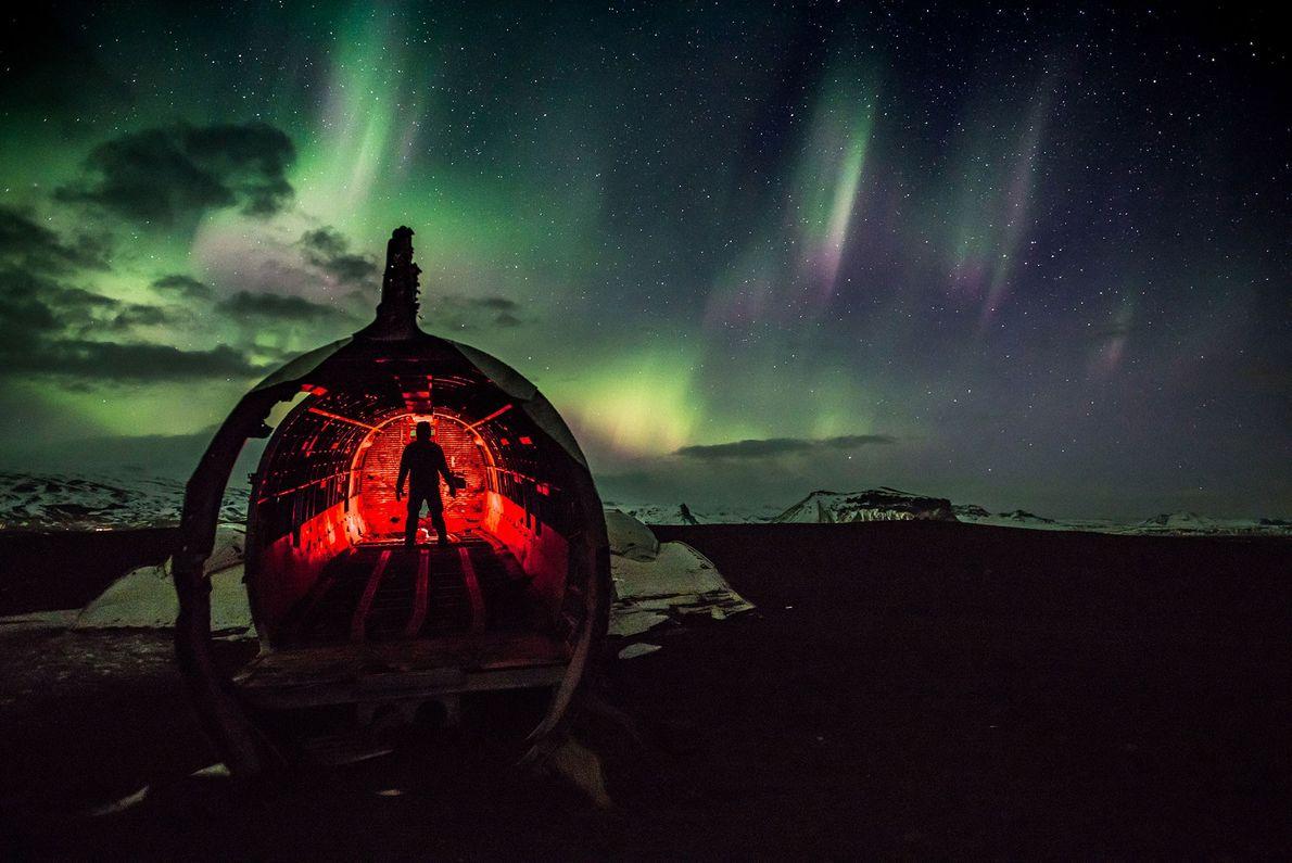 Um homem ilumina uma porção de um avião destruído abandonado no cenário vasto e invernal da ...