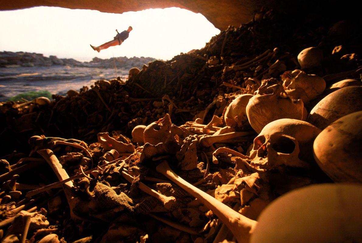 Um alpinista se pendura em frente à entrada cheia de ossos de uma caverna nos precipícios ...