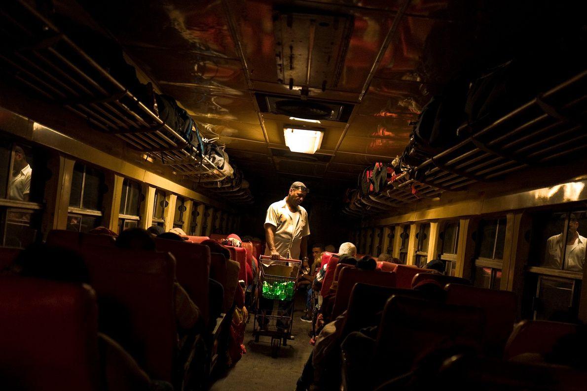 Um homem vende comida aos passageiros em uma viagem noturna de Havana para Santiago de Cuba.