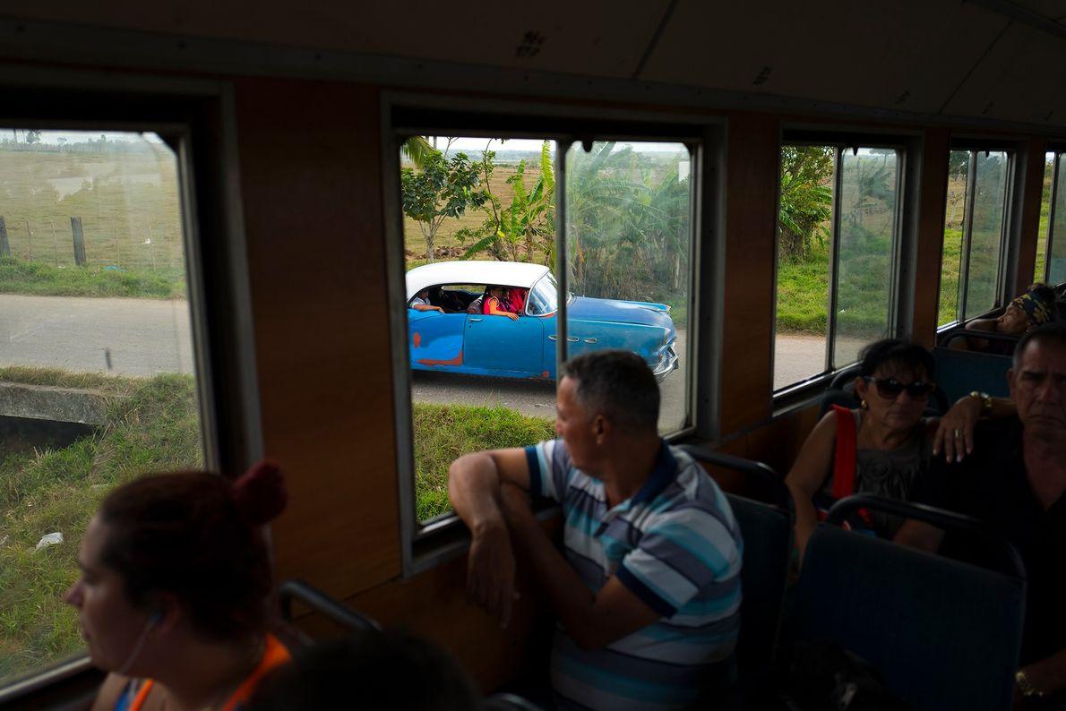 Um carro de passeio espera o trem passar a caminho de San Antonio de los Baños.